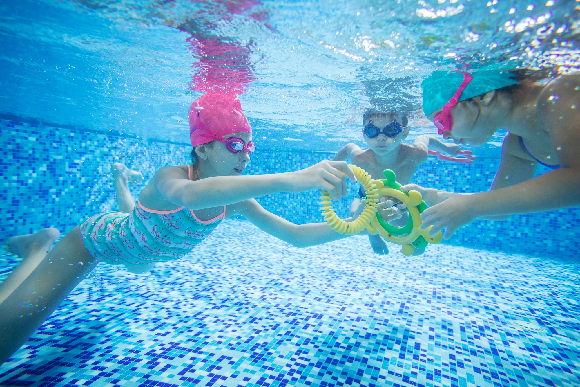 Kids swimming underwater and playing with toys